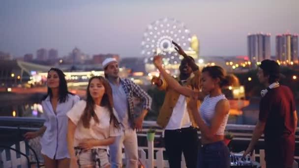 Lassú mozgás a táncoló tetőn élvezi a párt, miközben Dj jóképű srác vonzó fiatalok keverés zene speciális berendezéssel. Fél-, városi- és ifjúsági koncepció