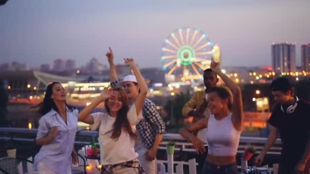 Zpomalený pohyb atraktivních mladých mužů a žen, tanec na střeše uvolňující a Bavíte se s hezký deejay směje, tleskání rukou a pomocí mixpultu