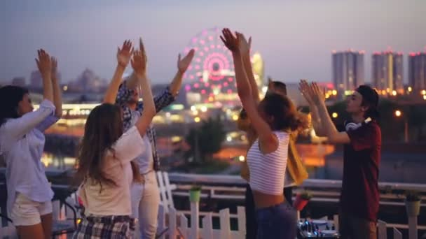 Slow motion of young people dancing and clapping hands at hight rooftop party with professional deejay. Men and women are having fun and relaxing at weekend.