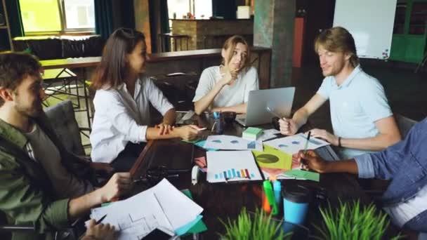 Multi-ethnischen Gruppe von Kollegen ist Diagramme und Grafiken während Team Meating am Schreibtisch im Büro sitzt und Austausch von Ideen diskutieren. Junge Menschen, Teamwork und Arbeitsplatz-Konzept