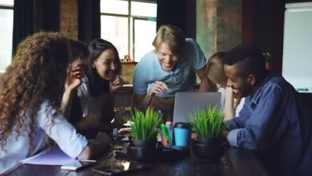 Gruppo Multiracial di colleghe è parlare e ridere seduta alla scrivania in ufficio di azienda di successo. Giovani indossano vestiti casual, laptop e documenti sono visibili