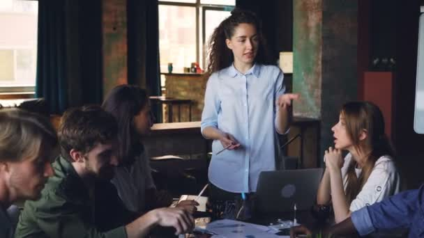 Confident young woman executive director is talking to multi-ethnic group of co-workers asking questions and giving orders during meeting in modern office.