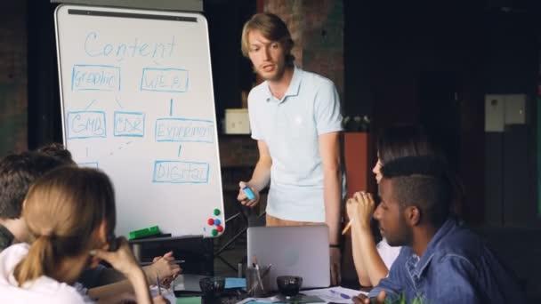 Mužské obchodní trenér pracuje s tabule ukazuje na graf a mluvící zaměstnanci společnosti jsou učení a mluvení sezení u stolu v kanceláři
