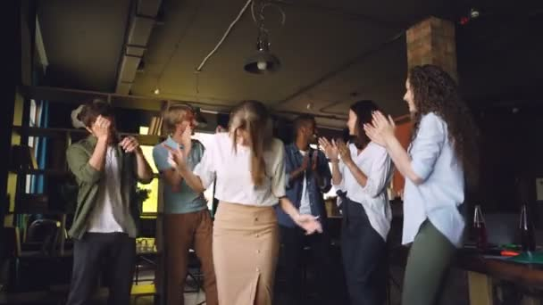 Company employees are dancing at corporate party in modern loft style office, attractive young men and women are having fun, clapping hands and laughing.
