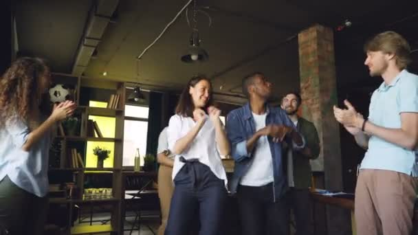 Caucasian and African American young people coworkers are dancing at office party having fun and clapping hands. Modern youth, corporate culture and holidays concept.