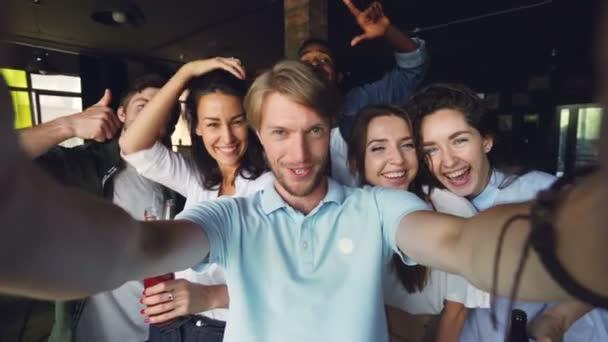 Skupina kolegů jsou společně s selfie, mladý muž drží kameru a pózování, jeho spolupracovníky jsou držení nápoje v lahvích, směje se a při pohledu na fotoaparát.