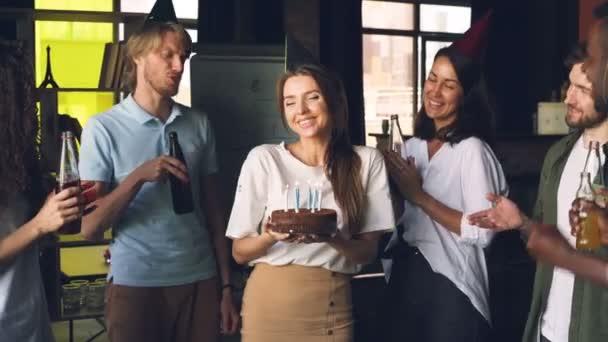 Zaměstnanci společnosti slaví narozeniny, Žena v ruce dort a foukání svíčky, její spolupracovníci jsou tleskali a cinkání lahví s nápoji