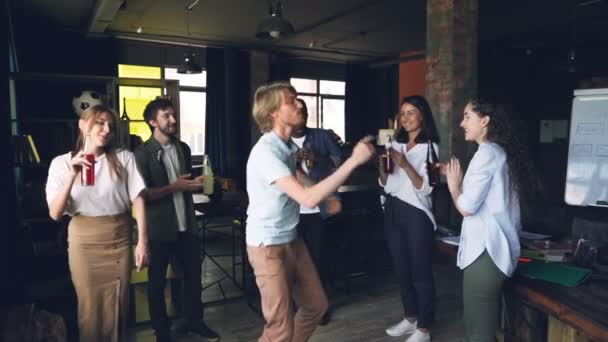 Slow motion of joyful young man dancing with his coworkers and having fun at office party with drinks and music. Happy people, holidays and work concept.