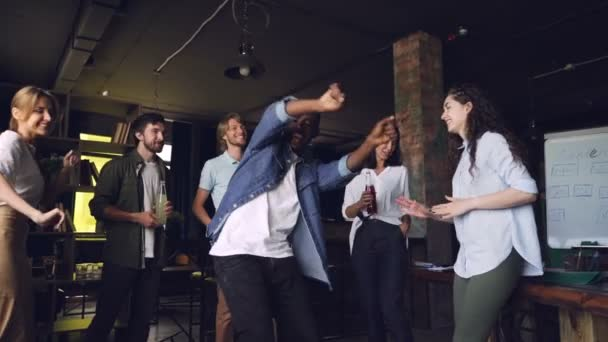 Slow motion of excited African American man dancing at corporate party in office with colleagues holding drinks. People are laughing and clapping hands.