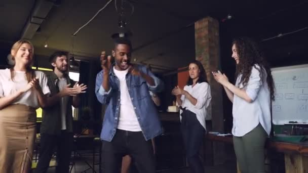 Slow motion of happy business owner African American young man dancing at corporate party with employees who are standing around and clapping hands.