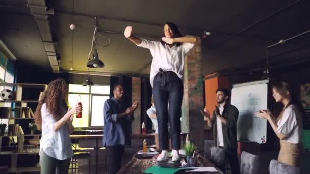 Slow motion of cheerful woman dancing on table in office at corporate party while her colleagues are standing around, looking at her, clapping hands and laughing.