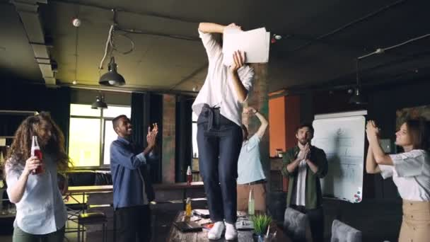 Clow motion of joyful young lady dancing on table at office party with pile of paper and throwing documents while her team is laughing and dancing around her.