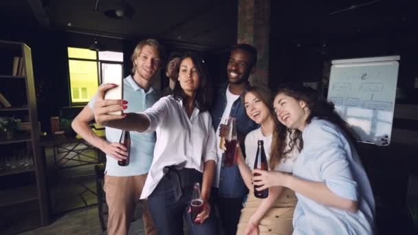Pretty lady is taking selfie with colleagues using smartphone, multi-ethnic group of people is posing with drinks and smiling. Men and women are wearing casual clothing.