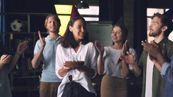 Slow motion of happy young lady holding birthday cake and blowing candles standing in office with colleagues clapping hands and congratulating her.