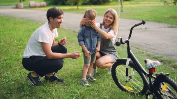 Milující rodiče dělají překvapení pro malého syna, zavřel oči a dává mu nové kolo jako dárek, šťastný chlapec je při pohledu na kolo a mluví s matkou a otcem.