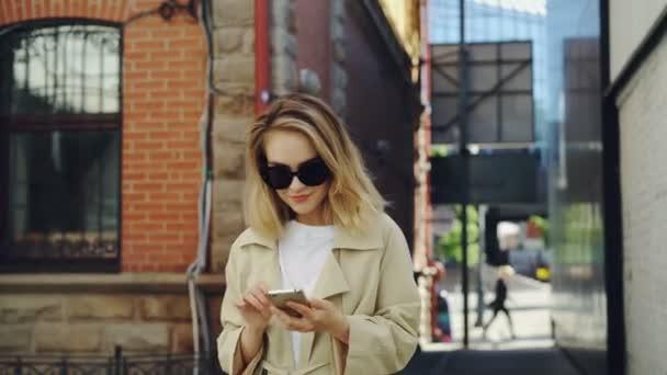 Krásná mladá dáma je stiskem smartphone a to pěšky ulicí v moderním městě. Technologie, krásné šťastní lidé a koncepce životního stylu mládeže