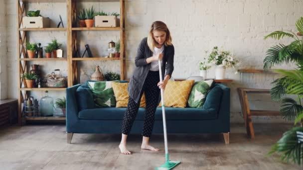 Hübsche blonde Hausfrau ist Hausarbeit Holzboden in schönen Wohnung Reinigung unter Sofa wischen. Mädchen konzentriert sich auf ihren Beruf, sie ist barfuß