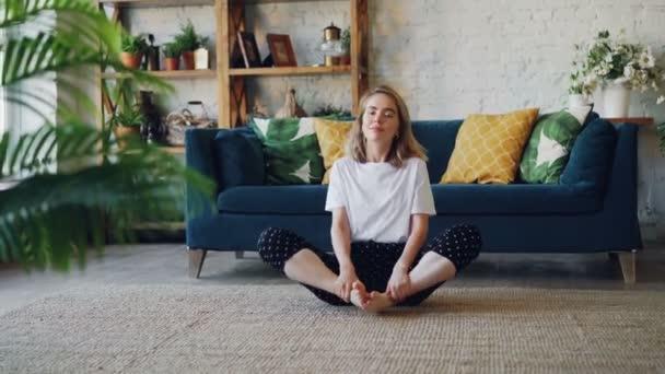 Hezká mladá žena je cvičení jógy na domácí relaxaci v jednoduché pozice sedí na podlaze s krásným nábytkem a okolí. Zdravý životní styl a lidé koncepce