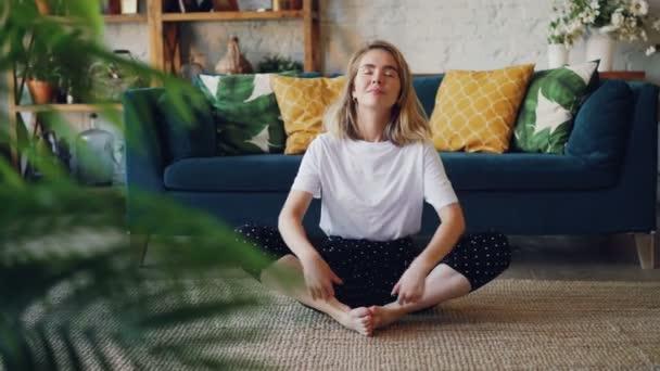 Flexibilní mladá dáma je relaxace v Badha Konasana pozici praxi Butterfly jóga pozice na domácí si odpočinek a relaxaci. Koncept pohody a lidé