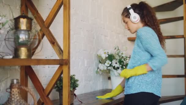 Attractive housewife is dusting the furniture and listening to the radio through wireless headphones and dancing, girl is wearing protective rubber gloves and casual clothing.