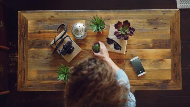 Pohled shora mladé ženy umístění kamery, rostliny a sluneční brýle na stole pak vyfotit s vytvářením smartphone strhat ležela fotografie. Design a koncepce moderních technologií