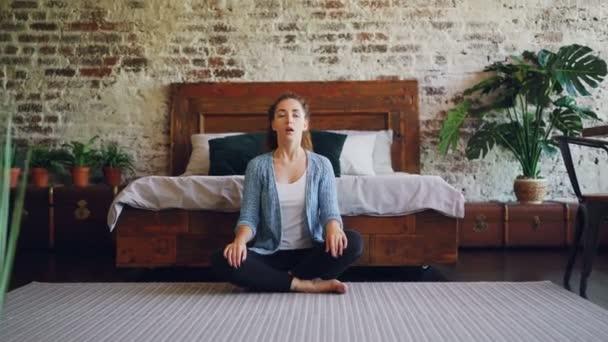 Mladá žena je cvičení jógy doma odpočívá v lotosu představují s rukama na kolenou a dýchání. Meditace, zdravého životního stylu a moderní ložnice