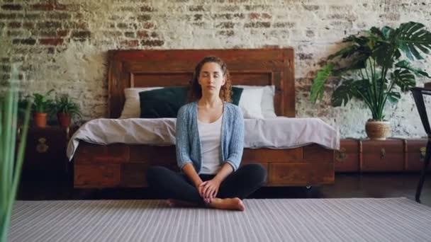 hübsches schlankes Mädchen mit langen Haaren entspannt in Lotus-Pose auf dem Schlafzimmerboden sitzend und atmet ein und aus. schöne Wohnung im Loft-Stil mit Bett, Teppich und Pflanzen ist sichtbar.