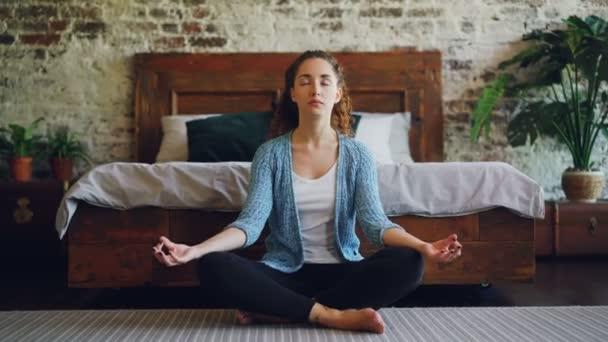Krásná mladá dáma sedí v lotosové pozici na podlahu ložnici a těší meditace, harmonii a mír. Moderní domy, zdravých lidí a zbytek koncepce