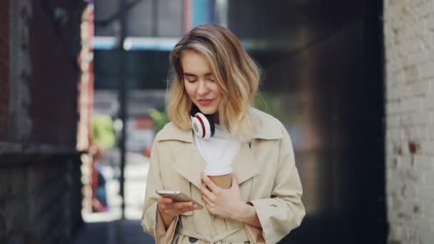 Zpomalené krásná mladá dáma drží smartphone dotknete obrazovky a venku pití kávy na cestách. Městský životní styl, take away nápoje a koncepce moderních technologií