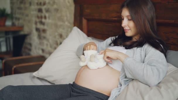 Těhotná dívka milující matka je uvedení dětské boty na její velké břicho a chůzi na dítě uhodit hrát s nenarozené dítě odpočívá na dvojlůžko doma