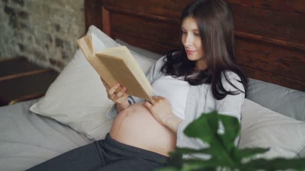 Krásná těhotná žena čte knihu ležící v posteli doma a usmívá se těší literatury. Šťastné těhotenství, literatura, hobby a mladých lidí koncepce.
