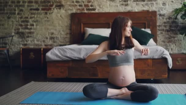 Sportovní žena nastávající matka dělá cvičení doma sedí na jógu a otáčení textu vlevo a vpravo těší aktivity. Těhotenství a koncept zdravého životního stylu