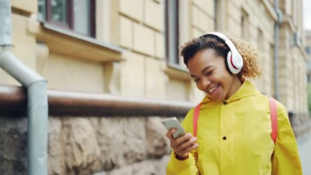 Happy African American girl is listening to music through wireless headphones and using smartphone walking outdoors enjoying song and walk. Gadgets and millennials concept.