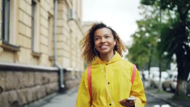 Gondtalan afrikai amerikai hallgató gyaloglás, hallgató-hoz zene keresztül fülhallgató és szabadidő énekelni. A modern technológia, ifjúsági kultúra, városok és emberek koncepció.