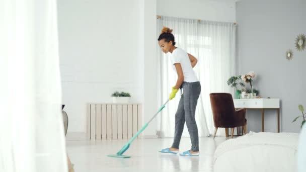 Mladá africká americká žena je čištění podlahy v moderním domě s mopem, hezká dívka, která nosí domů oblečení, přezůvky a gumové rukavice se soustředí na práci.