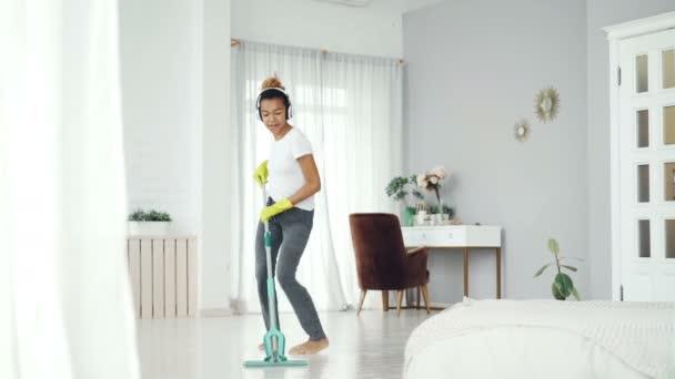 Šťastné domácnosti dělá domácí práce a poslech hudby na sobě moderní bezdrátová sluchátka, mladá dáma je v mop chozeni baví doma