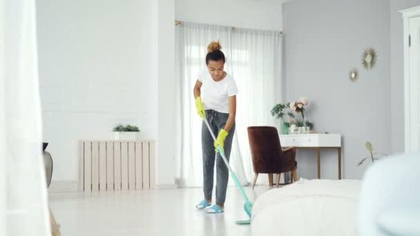 Docela africká americká dívka je vytírání podlahy doma s plochou plastovou mop na sobě rukavice a oblečení oblečení at-home. Moderní interiéry, čistotu a lidé koncepce.