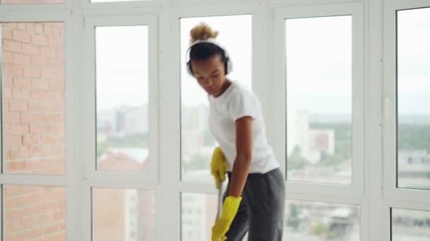Creative Smíšené rasy žena poslechu hudby ve sluchátkách, tančí a zpívá během čištění up doma, holka je mytí podlahy a mají baví rutinní práce.