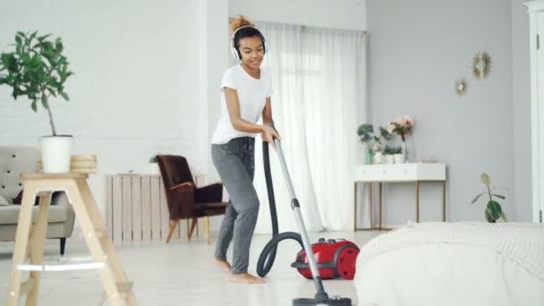 Die fröhliche Hausfrau benutzt beim Aufräumen zu Hause Staubsauger, hört über Kopfhörer Musik, tanzt und singt. Technologie und Menschen-Konzept.