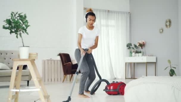 Kreative afrikanisch-amerikanische Teenager saugen Boden in schöner Wohnung, hören Musik mit Kopfhörern, tanzen und singen. Elektrogeräte und Spaßkonzept.