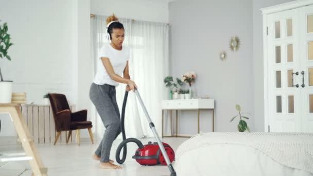 fröhliche Mischlingshündin saugt Boden in modernem Haus und genießt Rockmusik singend und tanzend mit Staubsauger. Elektrogeräte und Spaßkonzept.