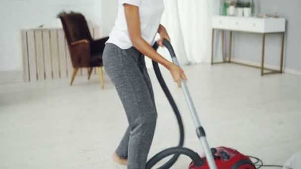 Aktive Hausfrau räumt Wohnung mit Staubsauger auf und hört Musik mit Kopfhörern, tanzt und singt. Freude, Hausarbeit und Jugendkonzept.
