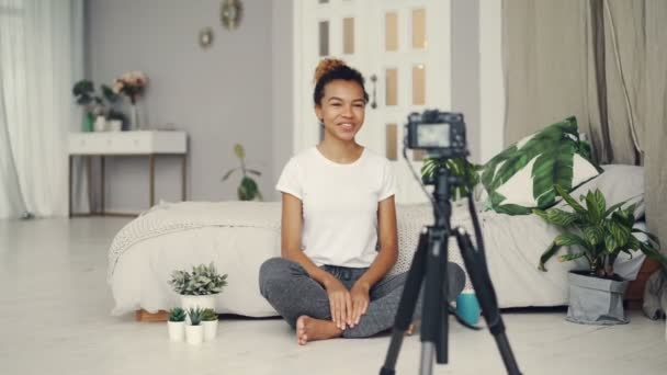 Good-looking African American girl creative blogger is recording video about plants sitting on floor of her apartment and talking looking at camera on tripod.