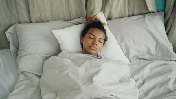 Mladá africká americká žena spát v pohodlné posteli pod teplou deku s odpočinek na krásné povlečení. Pohodlí, odpočinek lidí a ložnice koncept.