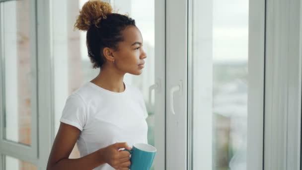 S úsměvem mladá žena pije čaj stál u okna a díval se mimo využití volného času doma. Apartmány, nápoje a lidé koncepce.