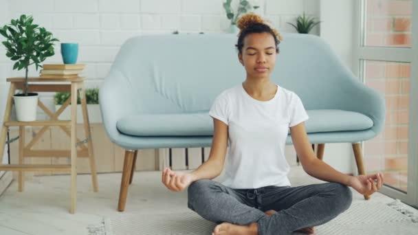 Ziemlich gemischtes Rennen Mädchen ist auf Boden in Lotus-Position mit den Händen auf den Knien sitzen und meditieren, genießen Sie Entspannung und Ruhe. Yoga, Volk und Heimat-Konzept