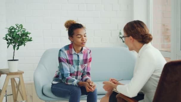 Afrikanerin spricht mit Psychologin, die im modernen Loft-Studio auf dem Sofa sitzt und lächelt, während ihr der Fachmann zuhört und Notizen macht.