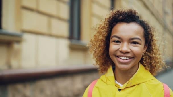 Detail zpomalené portrét roztomilé Smíšené rasy mladá dáma s úsměvem a při pohledu na fotoaparát s budovami a stromy v pozadí. Koncept pozitivity a lidé