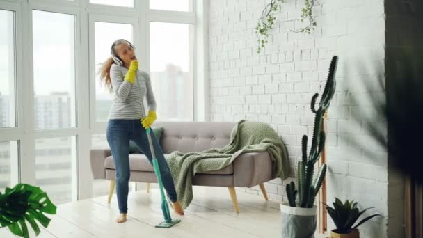 Joyful girl is mopping floor in light apartment and having fun listening to music through headphones, dancing and singing. Beautiful furniture and plants is visible.