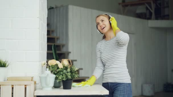 Happy young housewife in rubber gloves is listening to music through headphones and singing during clean-up at home, girl is dusting the furniture and having fun.